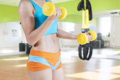 Woman trains arms muscle with two dumbbells Royalty Free Stock Photo