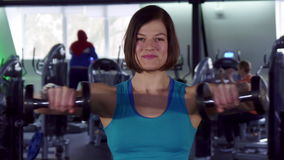 Woman trains with dumbbells. Attractive sportswoman training with dumbbells at the gym. Close up of pretty female athlete raising her arms to the sides. Strong