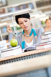 Woman trains at the library. Woman with green apple surrounded with piles of books reads sitting at the table at the library. Studying Royalty Free Stock Images