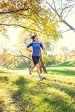 Woman trains in nature. Runner in flight phase. The girl runs through the autumn park. Slender woman trains in nature. Sports in the forest. Brunette runs along royalty free stock photos