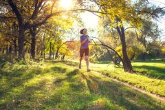 Woman trains in nature. Runner in flight phase. The girl runs through the autumn park. Slender woman trains in nature. Sports in the forest. Brunette runs along royalty free stock photo