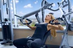Woman trains pecs in gym. Woman trains pecs in the gym royalty free stock photo