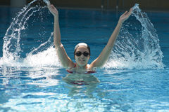 Woman trains synchronous swiming. At water pool Stock Photography