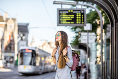 Woman on the tram station. Young woman standing on the tram station with time table in the old town of Gent city in Belgium Stock Photo