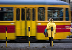 Woman at a tram stop. Belgrade, Serbia - November 18, 2016: Woman in yellow coat at a bus stop and a yellow red tram passing in motion blur Stock Photos