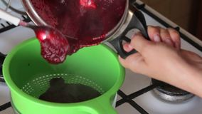 A woman transfers cranberries cooked with sugar from a saucepan into a colander. Prepares mashed potatoes for marshmallow. A woman transfers cranberries cooked stock footage
