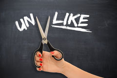 "Woman transforming the word ""unlike"" to the word ""like"" by cutting the prefix with scissors Stock Photo"