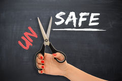 "Woman transforming the word ""unsafe"" into ""safe"" with scissors Royalty Free Stock Photography"