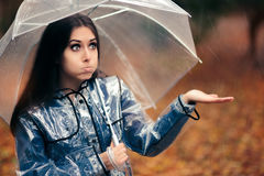 Woman with Transparent Raincoat and Umbrella Checking for Rain Stock Photography