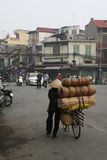 A woman is transporting goods on her bike in a street of Hanoi (Vietnam) Stock Photo