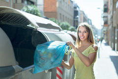 Woman with trash bags near garbage bin Stock Images