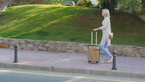 Woman with travel bag goes along the resort area. On a clear sunny day stock video