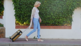 Woman with travel bag goes down the resort area. On a clear sunny day stock video