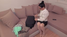 Woman with travel bag at home before journey. In room stock video