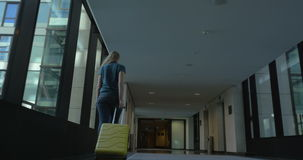 Woman with travel bag leaving hotel stock footage