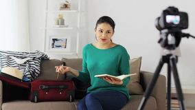 Woman with travel bag recording video at home stock video