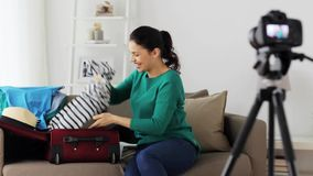 Woman with travel bag recording video at home. Blogging, tourism, technology, mass media and people concept - happy smiling woman or blogger with camera stock footage