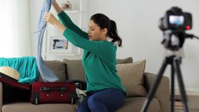 Woman with travel bag recording video at home. Blogging, tourism, technology, mass media and people concept - happy smiling woman or blogger with camera stock video
