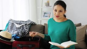 Woman with travel bag recording video at home. Blogging, tourism, technology, mass media and people concept - happy smiling woman or blogger with camera and stock footage