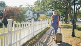 A woman with a travel bag on wheels is walking along the sidewalk. A typical American town. Rear view. Steadicam shot. A woman with a travel bag on wheels is stock footage