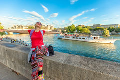 Woman travel freedom. Traveler freedom concept. Caucasian lifestyle woman with open arms enjoying the Seine. Bateau-mouche and Pont Neuf on a blurred background Royalty Free Stock Photo