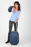 Woman with travel luggage. A woman with luggage on wheels Stock Photo