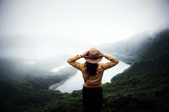 Woman traveler in Azores. Woman traveler holding hat and looking at amazing mountains and forest, wonderful travel concept, space for text, atmospheric epic stock photos