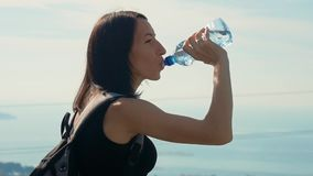 Woman traveler with backpack drinking water from a bottle. Healthy hiker girl drinking water in nature hike. Woman traveler with backpack drinking water from a stock footage