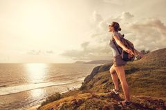Woman traveler with backpack enjoying sunset view on mountain co. Carefree tourist with backpack standing on top of a mountain and enjoying sunset view. Island stock photo