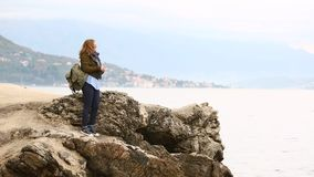 A woman traveler with a backpack is standing on a rock on the sea. A woman traveler with a backpack enters the frame, stops on a rock and throws coins into the stock footage