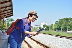 Woman traveler with backpack and hat looking the map at th. Young woman traveler with backpack and hat looking the map at the train station Stock Photography