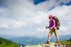 Woman Traveler with Backpack hiking in the Mountains. Active life and sport concept stock image
