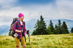 Woman Traveler with Backpack hiking in the Mountains. With beautiful summer landscape stock image