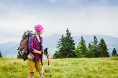 Woman Traveler with Backpack hiking in the Mountains. With beautiful summer landscape stock photography