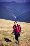 Woman Traveler with Backpack hiking in Mountains with beautiful Stock Image
