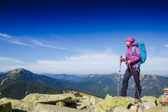 Woman Traveler with Backpack hiking in the Mountains. With blue sky background royalty free stock image