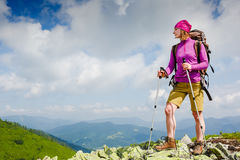 Woman Traveler with Backpack hiking in the Mountains. Woman Traveler with Backpack hiking in the sunny Mountains royalty free stock image