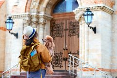 Woman traveler with backpack holding dog examines architectural monument . royalty free stock photography