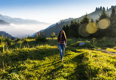 Woman traveler with backpack holding hat and looking at amazing mountains and forest, wanderlust travel concept, space Stock Photos