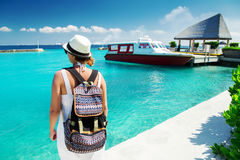 Woman traveler with backpack near boat at tropical island Stock Image