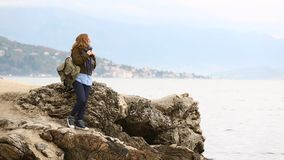 A woman traveler with a backpack is standing on a rock on the sea. Woman traveler with a backpack is standing on a rock on the sea coast on a background of stock video