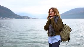 Woman traveler with a backpack is standing on the sea coast stock footage