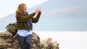 A woman traveler with a backpack is standing on a rock on the sea. A woman traveler with a backpack stands on a rock on the sea shore against the backdrop of the stock footage