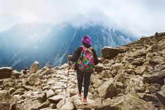 Woman traveler backpack tracking sticks top mountain Mount Rysy. Woman traveler with backpack and tracking sticks on top mountain. Travel and backpacking stock photo
