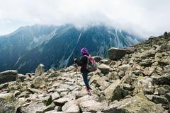 Woman traveler backpack tracking sticks top mountain Mount Rysy. Woman traveler with backpack and tracking sticks on top mountain. Mount Rysy, high tatras stock image