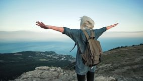 Woman traveler with backpack walking and enjoying view at mountains. Traveling along mountains, freedom and active lifestyle concept stock video footage