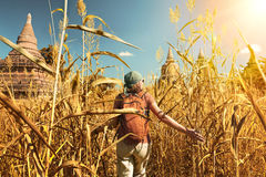 Woman traveler with a backpack walking through field to ancient Royalty Free Stock Photo