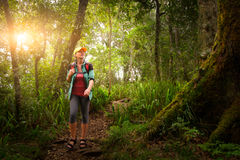 Woman traveler with backpack walking in rain forest. Woman traveler with backpack walking along the trail in the rain forest. Island Lombok, Indonesia stock images