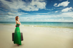 Woman traveler at the beach with suitcase talking on mobile phone royalty free stock photos