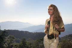 Woman traveler. Beautiful, young, red-haired girl tourist standing on top of a mountain with a camera stock images